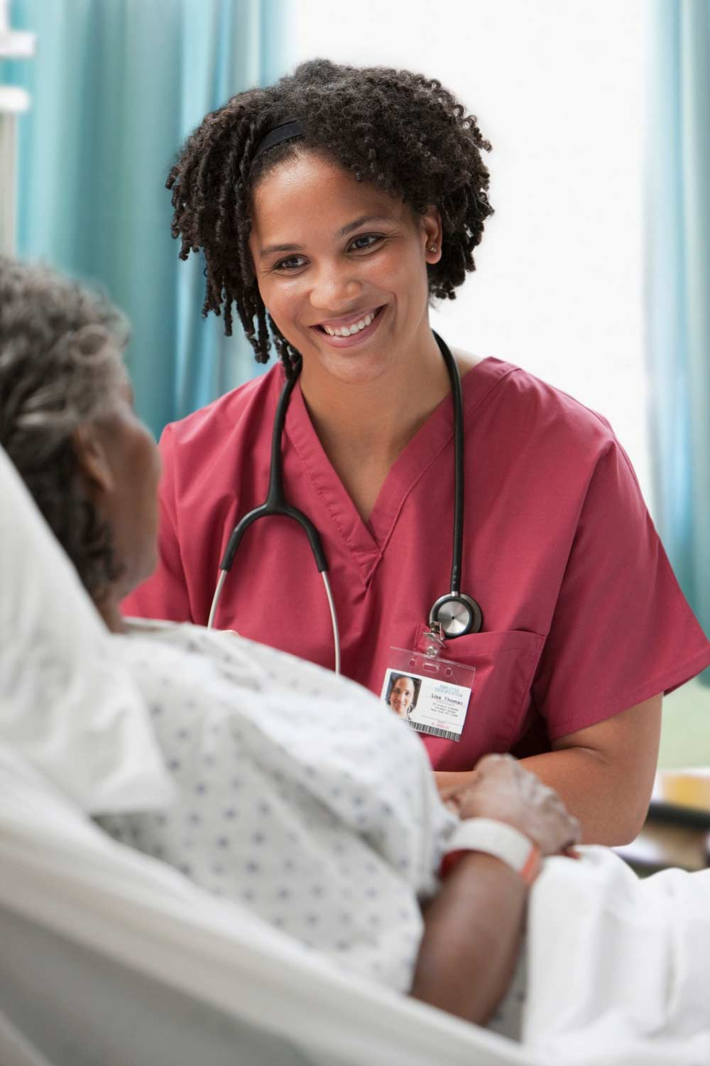 healthcare provider smiling and listening to hospital patient