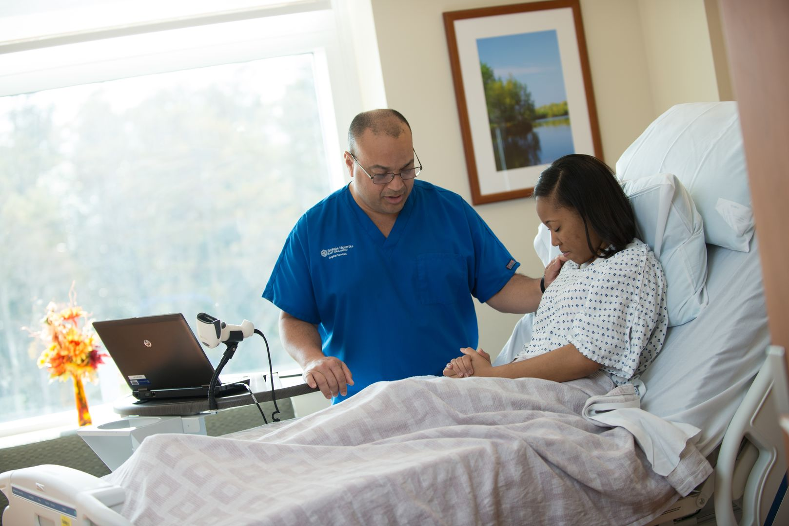 nurse praying with hospital patient