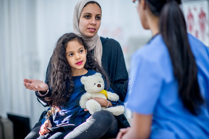 nurse talking with muslim mother and daughter in the emergency department