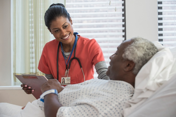 Female nurse talking with male hospital patient