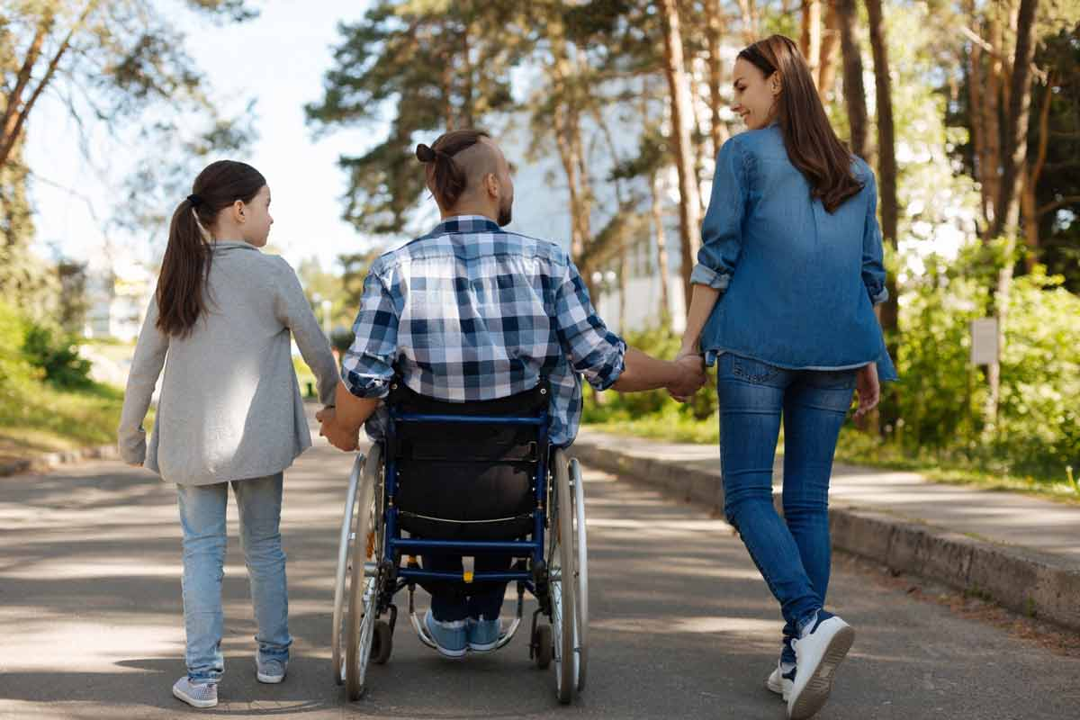 family walking with man in wheelchair